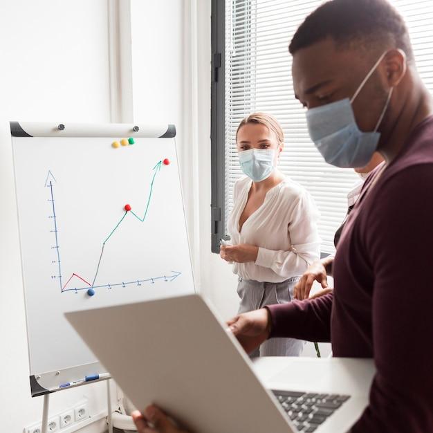 Pessoas trabalhando no escritório durante a pandemia usando máscaras médicas e sendo produtivas Foto Premium