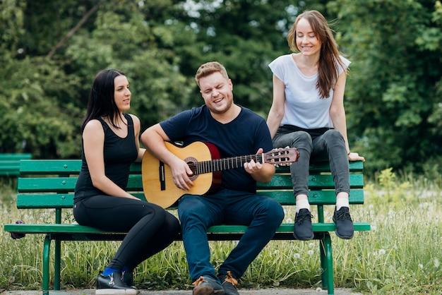 Pessoas unidas relaxando no banco cantando e tocando guitarra Foto gratuita