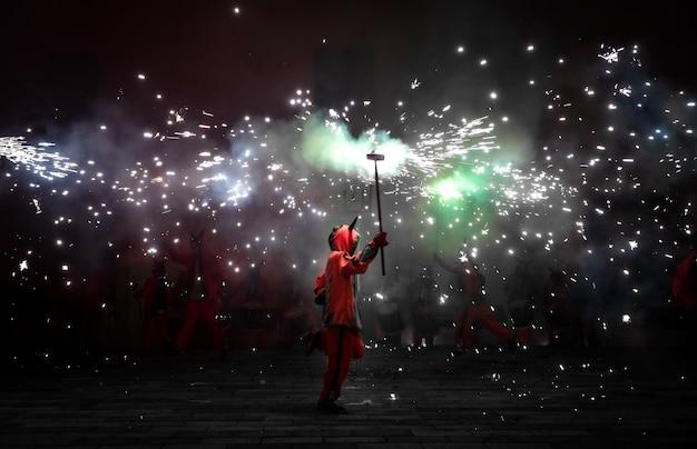 Pessoas vestidas como demônios dançando com fogos de artifício Foto Premium