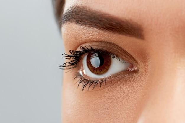 Pestanas pretas compridas. close da bela sobrancelha feminina e olho grande com cílios postiços. mulher com pele saudável suave macia e maquiagem facial profissional glamourosa. Foto Premium