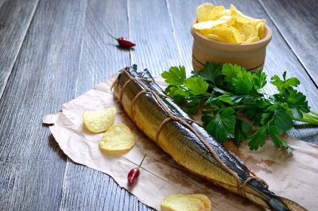 Petiscos de cerveja. peixe defumado, batatas fritas em uma mesa de madeira. sauro defumado artesanal. Foto Premium