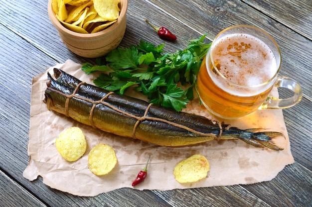 Petiscos de cerveja. peixe defumado, batatas fritas, um copo de cerveja em uma mesa de madeira. Foto Premium