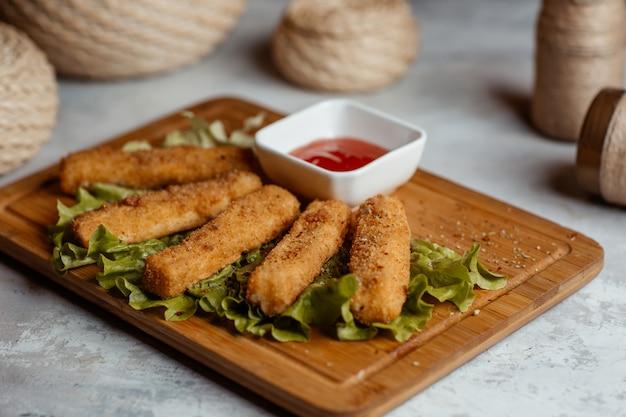 Petiscos de frango crocante, palitos com ketcup em uma placa de madeira com cestas rústicas ao redor Foto gratuita