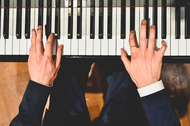 Pianista, executando uma peça em um piano de cauda com teclas brancas e pretas Foto Premium