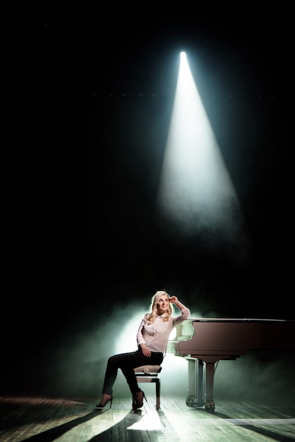 Pianista posando perto de piano branco no palco Foto Premium