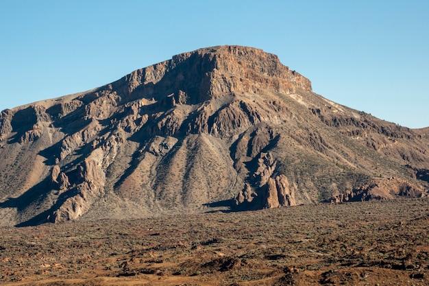 Pico da montanha solitária com céu claro no fundo Foto gratuita
