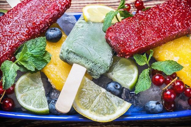 Picolés com frutas e bagas em uma mesa de madeira Foto Premium