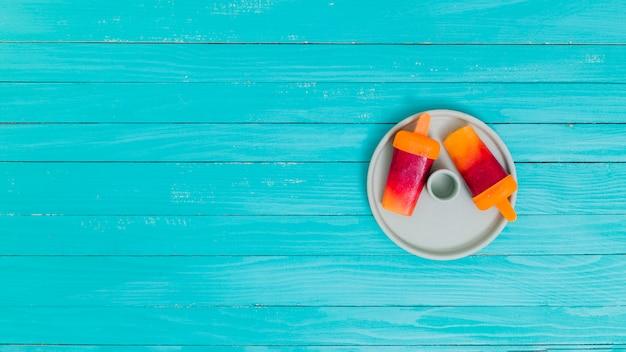 Picolés de frutas brilhantes no prato na superfície de madeira Foto gratuita