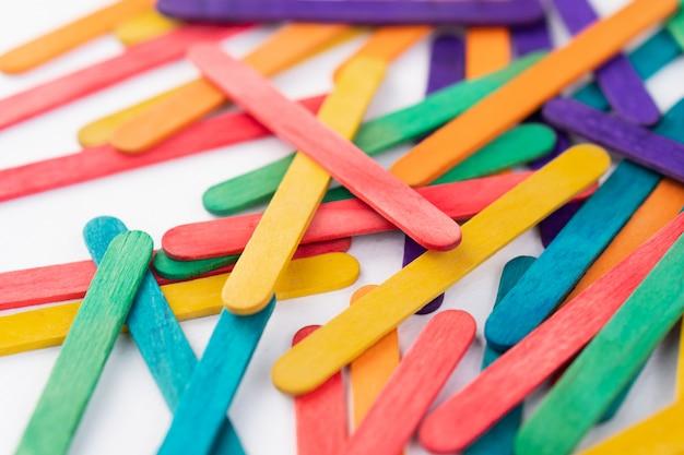 Picolés de madeira arco-íris colorido em papel branco, com espaço de cópia, varas de cor abstrata cobrir o quadro para trabalhos de artesanato de arte de crianças, crianças de volta ao conceito de escola Foto Premium