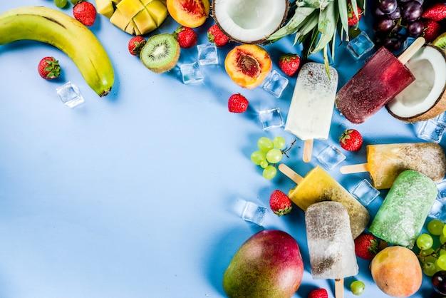 Picolés de sorvete tropical com sementes de chia e sucos de frutas - abacaxi, laranja, manga, banana, kiwi, coco, uvas, pêssego, morango Foto Premium