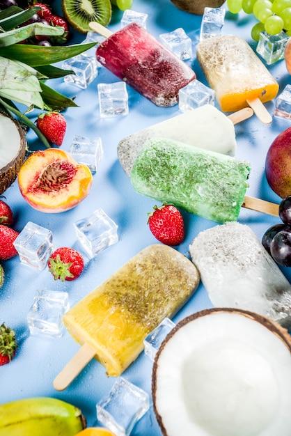 Picolés de sorvete tropical com sementes de chia e sucos de frutas - abacaxi manga laranja banana kiwi coco uvas pêssego morango cópia espaço Foto Premium