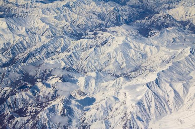 Picos de montanha na neve de uma janela de avião Foto Premium