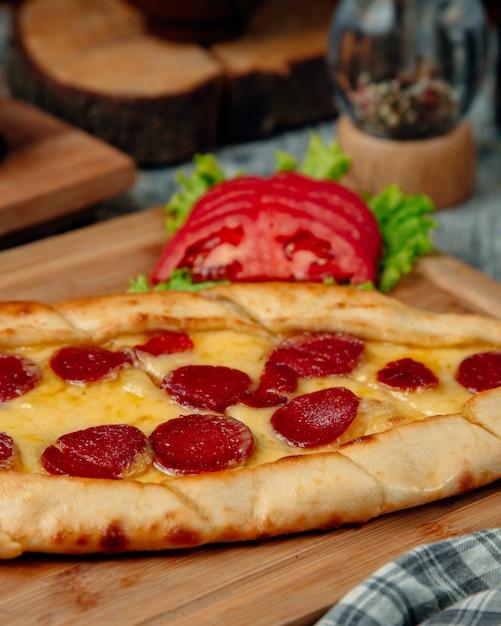 Pide de salsicha turca com tomate em cima da mesa Foto gratuita