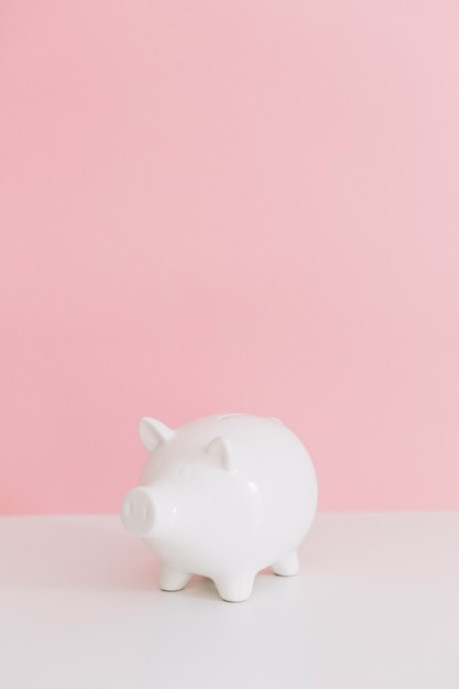 Piggybank branco na mesa branca sobre o fundo rosa Foto gratuita