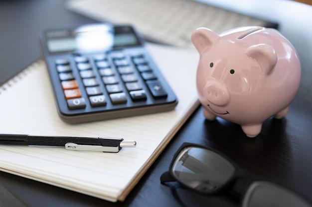 Piggybank e calculadora na mesa calculadora de documento de negócios contando dinheiro Foto Premium