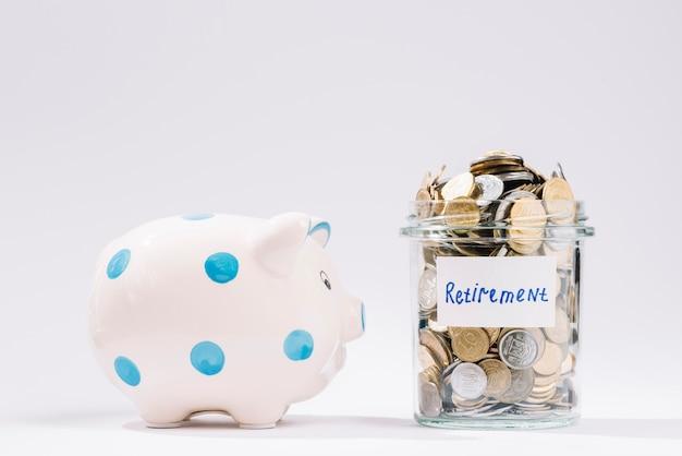 Piggybank perto de recipiente de aposentadoria cheio de moedas no pano de fundo branco Foto gratuita
