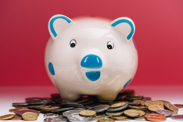 Piggybank sobre moedas na frente do fundo vermelho Foto gratuita