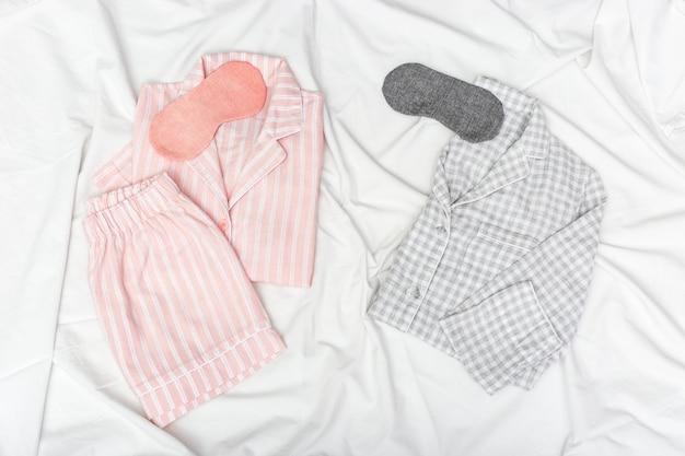 Pijamas cor-de-rosa e cinzento para duas pessoas, e máscara de sono para olhos em lençol de algodão branco. Foto Premium