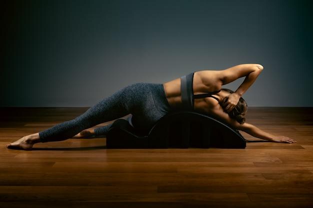 Pilates, aptidão, esporte, treinamento e conceito dos povos - mulher que faz exercícios em um tambor pequeno. conceito de fitness Foto Premium