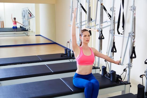 Pilates reformer lado mulher empurrar através do exercício Foto Premium
