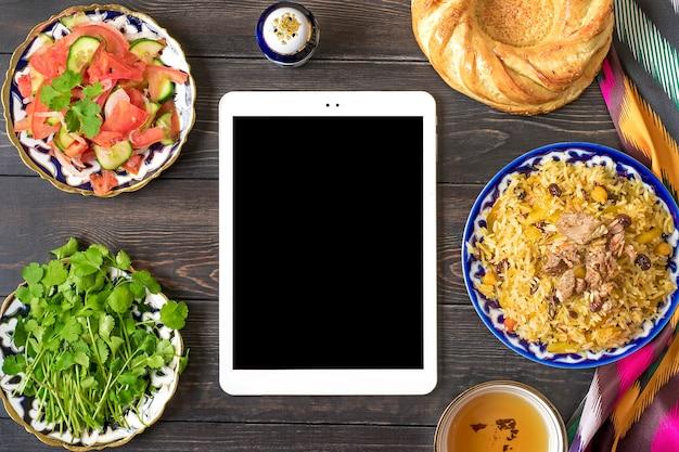 Pilau nacional uzbeque com carne no prato com padrão tradicional, tecido ikat, tablet em madeira Foto Premium