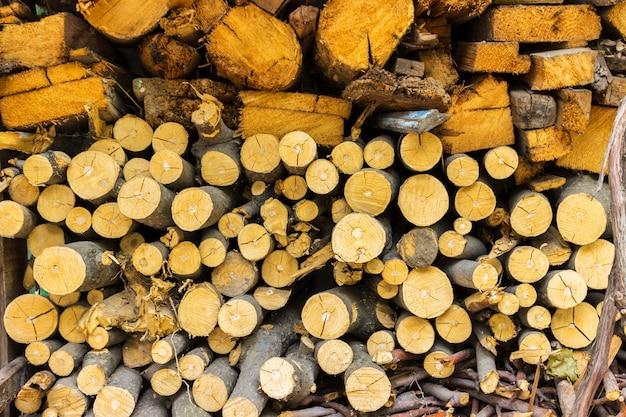 Pilha da lenha velha para o fundo. pilha de madeira de fogo picada preparada para o inverno Foto Premium