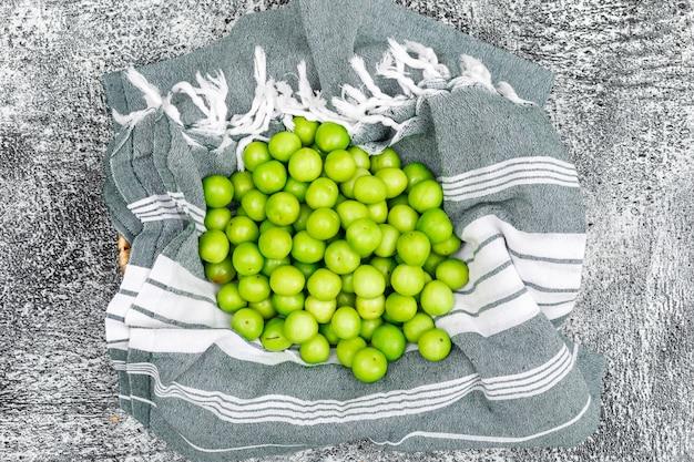 Pilha de ameixas verdes vista superior na toalha de cozinha e grunge Foto gratuita