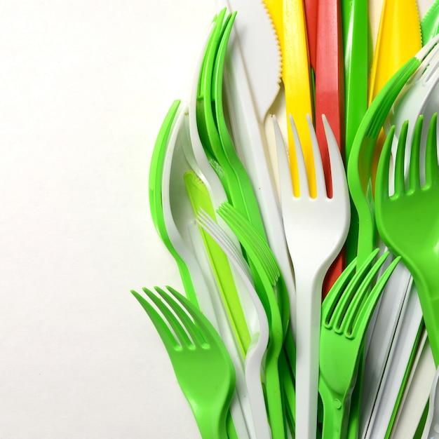 Pilha de aparelhos de uso único utensílios de cozinha de plástico amarelo, verde e branco brilhante Foto Premium