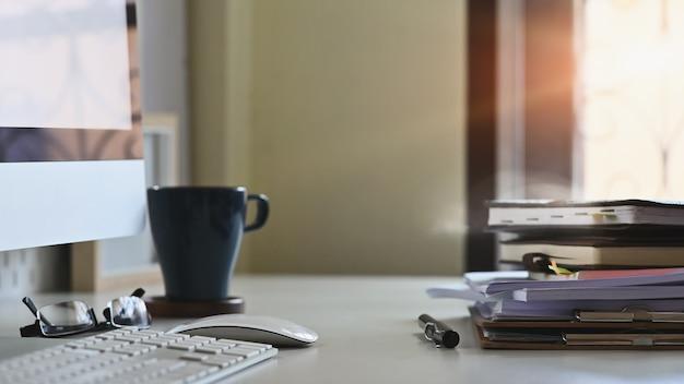 Pilha de arquivos em papel e equipamentos de negócios de caneta na mesa de escritório. Foto Premium