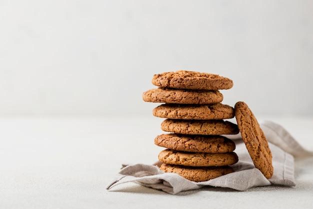 Pilha de biscoitos assados frescos em pano e fundo branco Foto gratuita