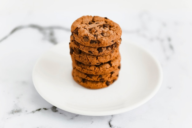 Pilha de biscoitos de chocolate assados na chapa branca sobre o fundo de mármore Foto gratuita