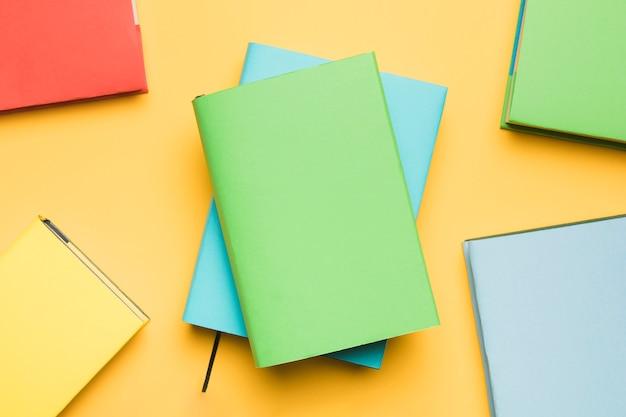 Pilha de blocos de notas, rodeados por livros coloridos Foto gratuita