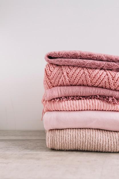 Pilha de blusas de malha no chão Foto gratuita