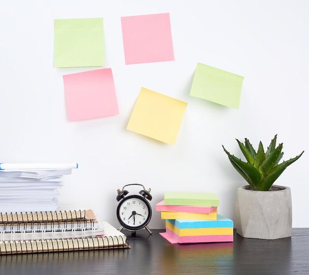 Pilha de cadernos de espiral e adesivos coloridos, ao lado de um vaso de cerâmica com uma flor em uma mesa preta Foto Premium