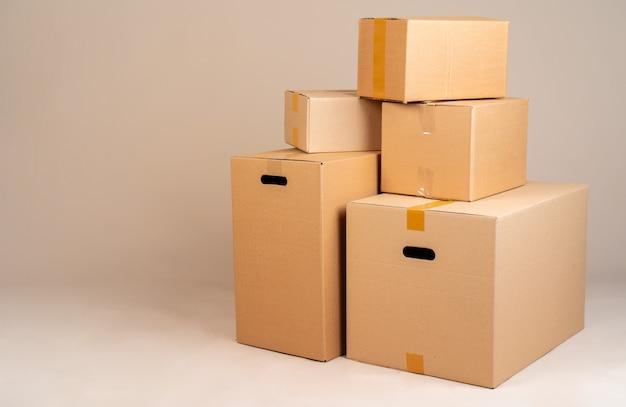 Pilha de caixas moxing marrons no fundo cinza Foto Premium