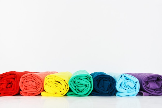 Pilha de camiseta colorida enrolada no fundo branco Foto Premium