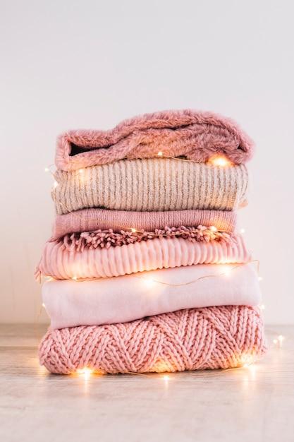 Pilha de camisolas de malha com festão no chão Foto gratuita