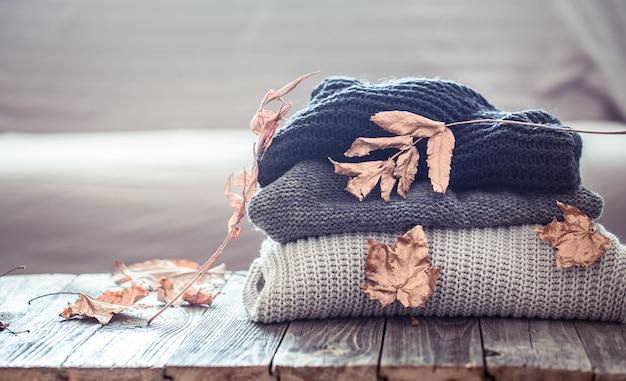 Pilha de camisolas de malha em uma mesa de madeira Foto Premium