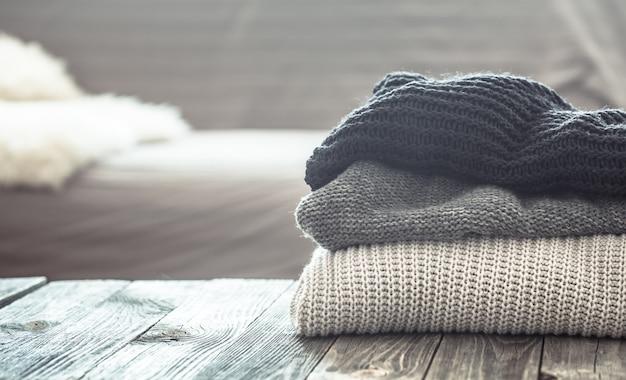Pilha de camisolas de malha em uma mesa de madeira Foto gratuita
