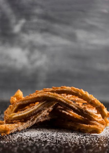 Pilha de churros com espaço para açúcar e cópia Foto gratuita