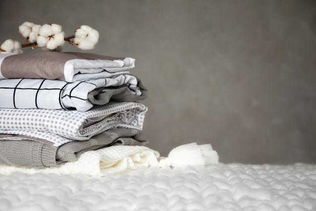 Pilha de cobertores quentes dobrados com diferentes padrões de design e galho de algodão em fundo cinza. cobertores de malha. produção de fibras têxteis naturais à base de plantas. fabricação. produto orgânico Foto Premium