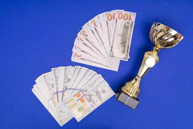 Pilha de copo de dinheiro e vencedor no fundo da mesa azul puro Foto Premium