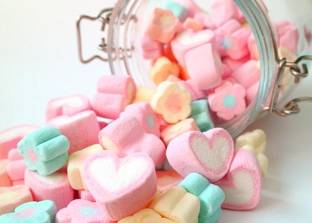 Pilha de cor pastel em forma de coração e flor em forma de doces de marshmallow espalhados de um frasco de vidro Foto Premium
