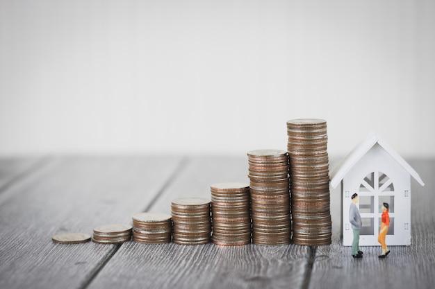 Pilha de dinheiro de moeda intensificar com casa branca, investimento de propriedade e hipoteca de casa financeira Foto Premium