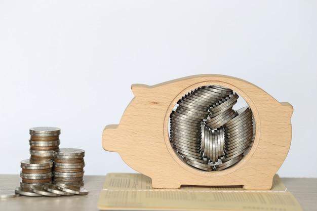 Pilha de dinheiro moedas na madeira mealheiro em fundo branco, poupar dinheiro para preparar no futuro e conceito de investimento Foto Premium