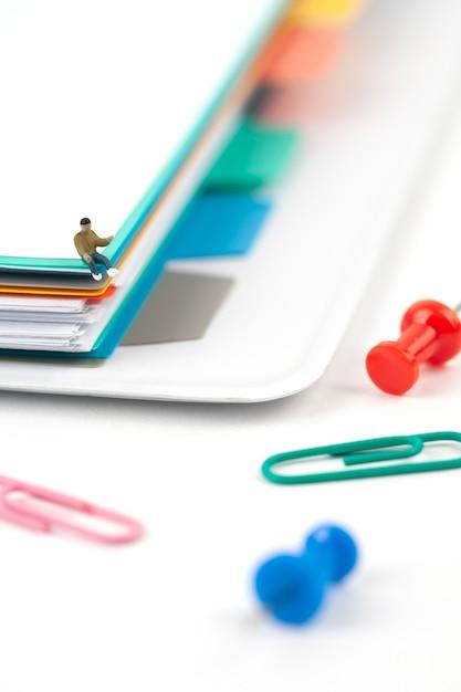 Pilha de documentos com homem em miniatura no fundo branco Foto Premium