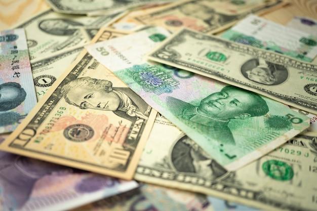 Pilha de dólar dos eua e notas de yuan chinês em cima da mesa Foto Premium