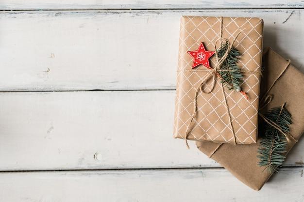Pilha de duas caixas de presente embrulhadas amarradas com fios na mesa branca que podem ser usadas como fundo de natal Foto Premium