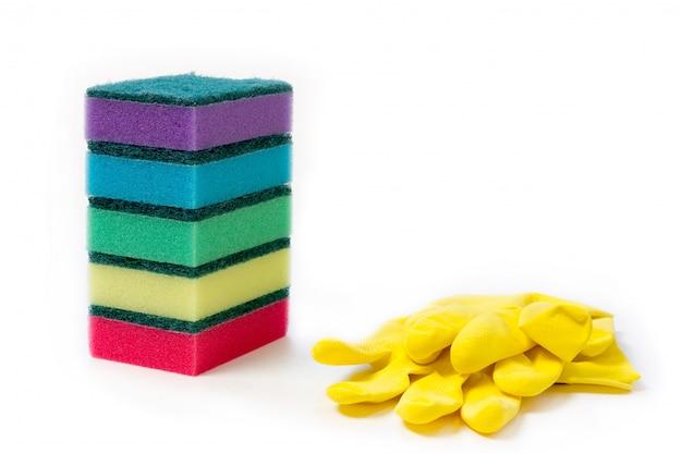 Pilha de esponja colorida e luvas de borracha amarela para limpeza molhada e lavar a louça no fundo branco com espaço para texto Foto Premium