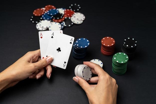 Pilha de fichas e mão de mulher com dois ases na mesa. conceito de jogo de poker Foto Premium